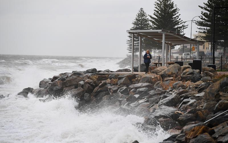 A woman takes a photo of the high tide and a storm surge at Brighton Beach, Adelaide as a storm front starts to hit the coast line in 2018. South Australia is set for two cold fronts this week.