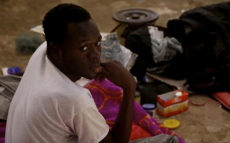 In this Wednesday, July 17, 2019 frame grab from video, a migrant sits on the floor in a detention center in the city of Sabha, which is about 650 kilometers, or 400 miles, south of the capital, Tripoli, Libya. Migrants held at a small, dilapidated detention center in the southern Libyan city of Sabha say they are being neglected by international organizations and often go hungry due to lack of food. (AP Photo)