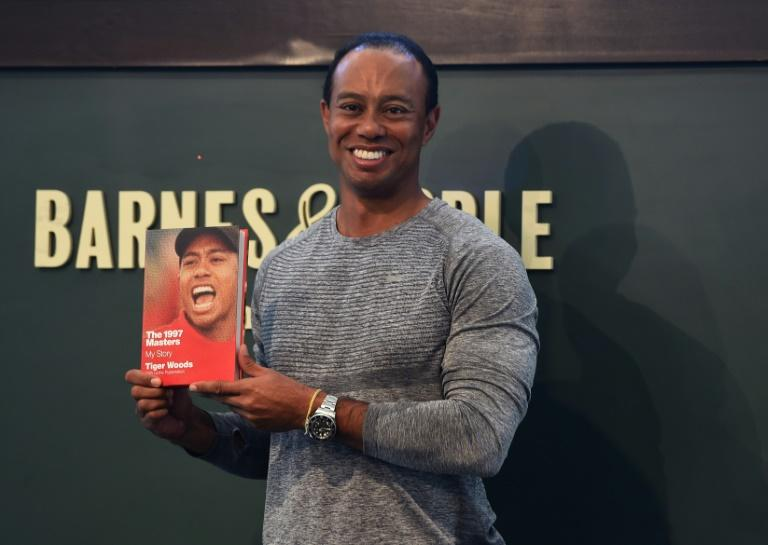 "The 14-time major champ golfer Tiger Woods holds a copy of his new book ""The 1997 Masters: My Story"" at a book signing in New York"