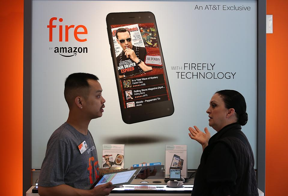 SAN FRANCISCO, CA - JULY 25:  An AT&T worker helps a customer with information on the new Amazon Fire phone at an AT&T store on July 25, 2014 in San Francisco, California.  Amazon's Fire phone is going on sale today at AT&T stores for $199 with a two-year AT&T contract or $649 without a contract. The phone features a year of Amazon Prime service, Dynamic Perspective 3D imaging and Firefly image recognition that allows users to scan objects and purchase the item from Amazon's online shopping site.  (Photo by Justin Sullivan/Getty Images)