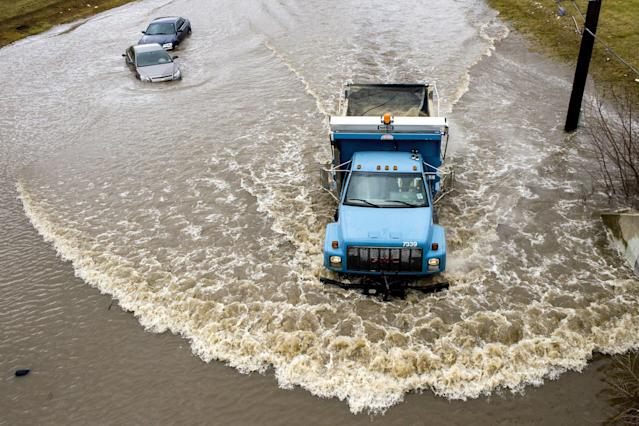 <p>A dirt truck plows through water, passing by two cars rendered unreachable by tow trucks after driving too deep into the the flooded street caused by heavy overnight rainfall on Wednesday, Feb. 21, 2018 in Flint, Mich. (Photo: Jake May/The Flint Journal-MLive.com via AP) </p>