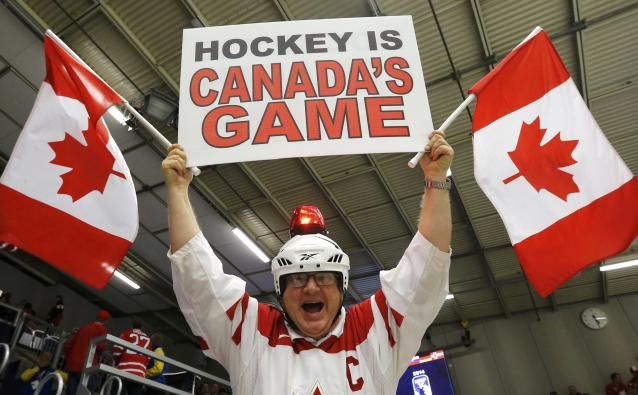 A Canadian fan cheers during play between Canada and the Czech Republic during the first period of their IIHF World Junior Championship ice hockey game in Malmo, Sweden, December 28, 2013. REUTERS/Alexander Demianchuk (SWEDEN - Tags: SPORT ICE HOCKEY)