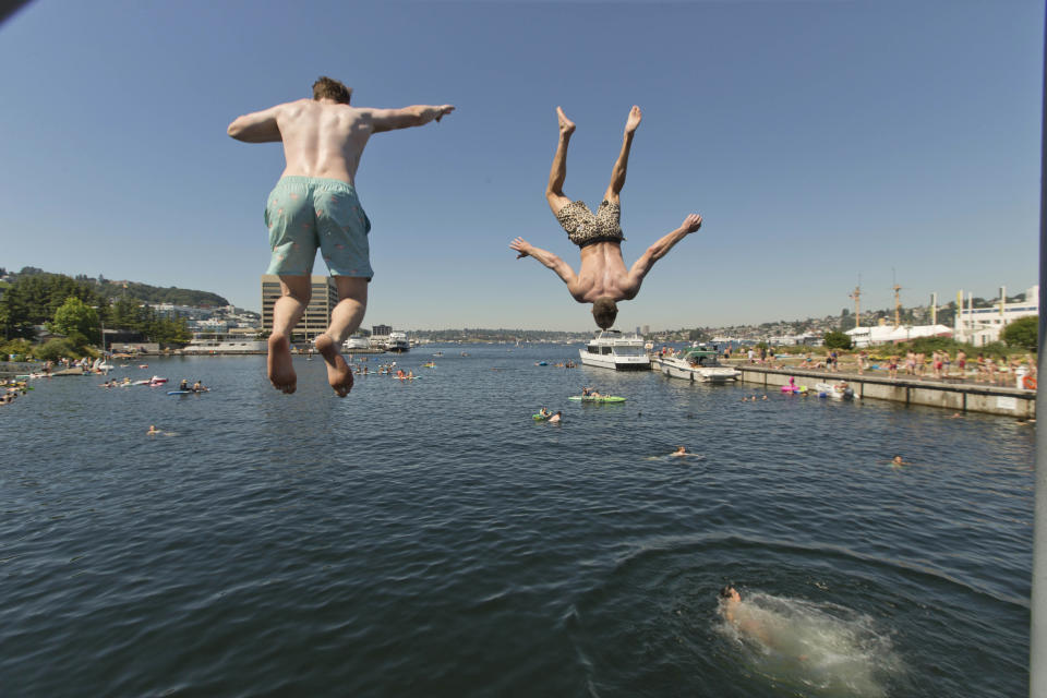 Two people jump from a pedestrian bridge at Lake Union Park into the water during a heat wave hitting the Pacific Northwest, Sunday, June 27, 2021, in Seattle. Yesterday set a record high for the day with more record highs expected today and Monday. (AP Photo/John Froschauer)