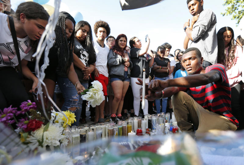 """Fans and mourners of rap singer XXXTentacion make an """"X"""" sign by a memorial, Tuesday, June 19, 2018, outside Riva Motorsports in Deerfield Beach, Fla., where the troubled rapper-singer was killed the day before. The 20-year-old rising star, whose real name is Jahseh Dwayne Onfroy, was shot and killed Monday in Florida in what police called an apparent robbery attempt. (AP Photo/Wilfredo Lee)"""