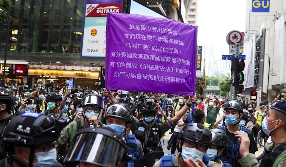 A police officer raises a flag warning demonstrators in Causeway Bay that they may be in violation of the national security law in October. Photo: Sam Tsang