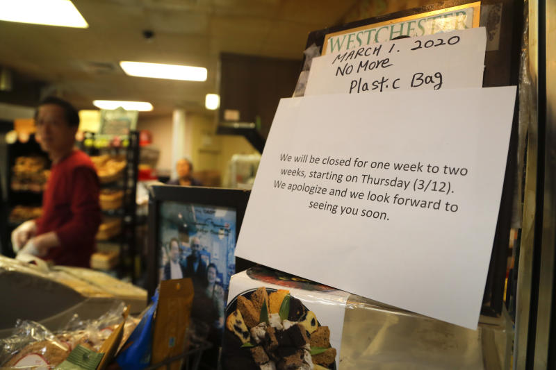 A notice hangs near the cash register at a bagel shop, Wednesday, March 11, 2020, in New Rochelle, N.Y. With business slowed since a cluster of coronavirus cases hit the New York City suburb, the shop will be closed beginning Thursday for the two weeks when the state enforces a containment area shuttering several schools and houses of worship and sending in the National Guard to help with what appears to be the nation's biggest cluster of coronavirus cases. (AP Photo/Julie Jacobson)