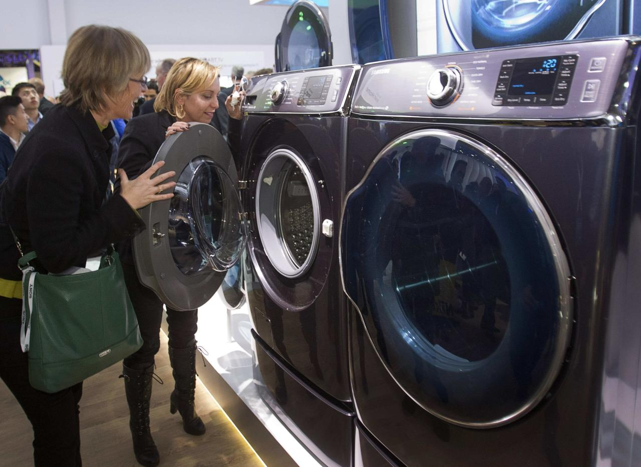 Kate Bulkley (L) and Susan Brazer look over the Samsung Electronics 9000 Series washer and dryer during the 2014 International Consumer Electronics Show (CES) in Las Vegas, Nevada, January 7, 2014. The washer and dryer are the world's largest, according to Samsung. REUTERS/Steve Marcus (UNITED STATES - Tags: BUSINESS SCIENCE TECHNOLOGY)