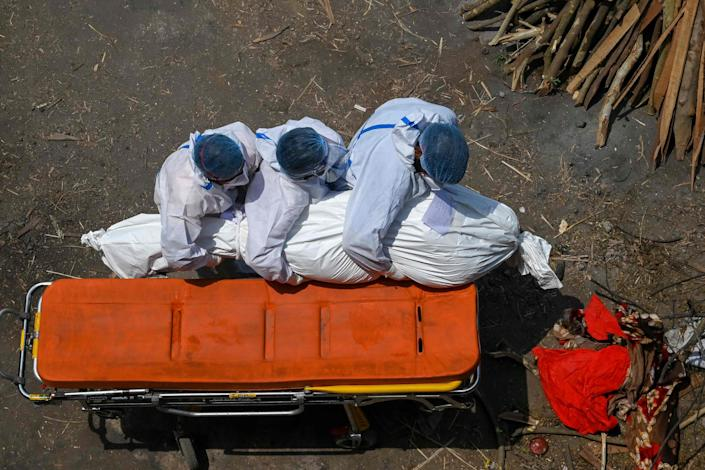 Family members and ambulance workers in PPE gear carry the body of a victim who died from COVID-19 complications to a cremation site in New Delhi, India on Tuesday.