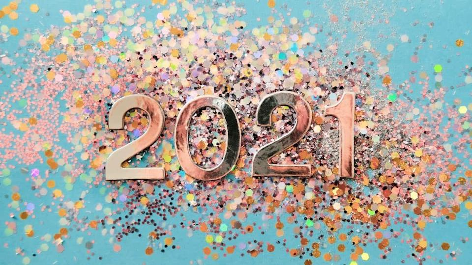 Silver and golden colorful Christmas glitters showing the year 2021 on turquoise background.