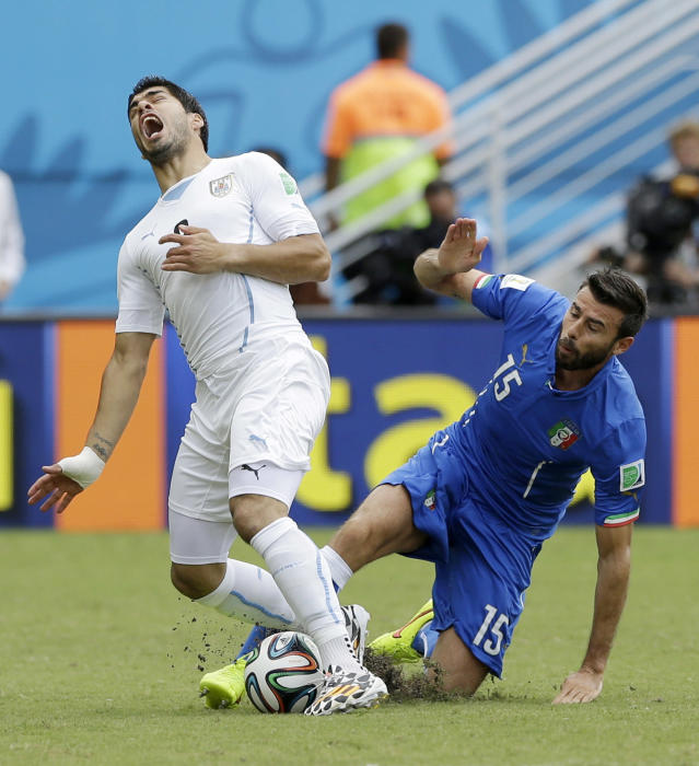 Uruguay's Luis Suarez is tripped up by Italy's Andrea Barzagli during the group D World Cup soccer match between Italy and Uruguay at the Arena das Dunas in Natal, Brazil, Tuesday, June 24, 2014. (AP Photo/Ricardo Mazalan)