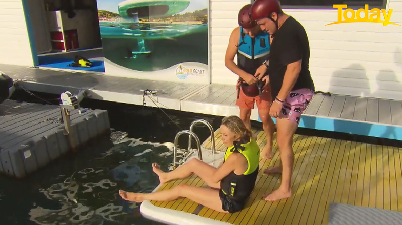 Today host Allison Langdon sits on a pontoon after injuring her knee during a watersports activity for the show as co-host Karl Stefanovic looks on