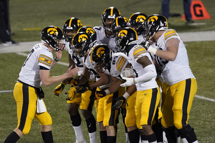 Iowa quarterback Spencer Petras calls a play in the huddle during the second half of an NCAA college football game against Illinois Saturday, Dec. 5, 2020, in Champaign , Ill. Iowa won 35-21. (AP Photo/Charles Rex Arbogast)