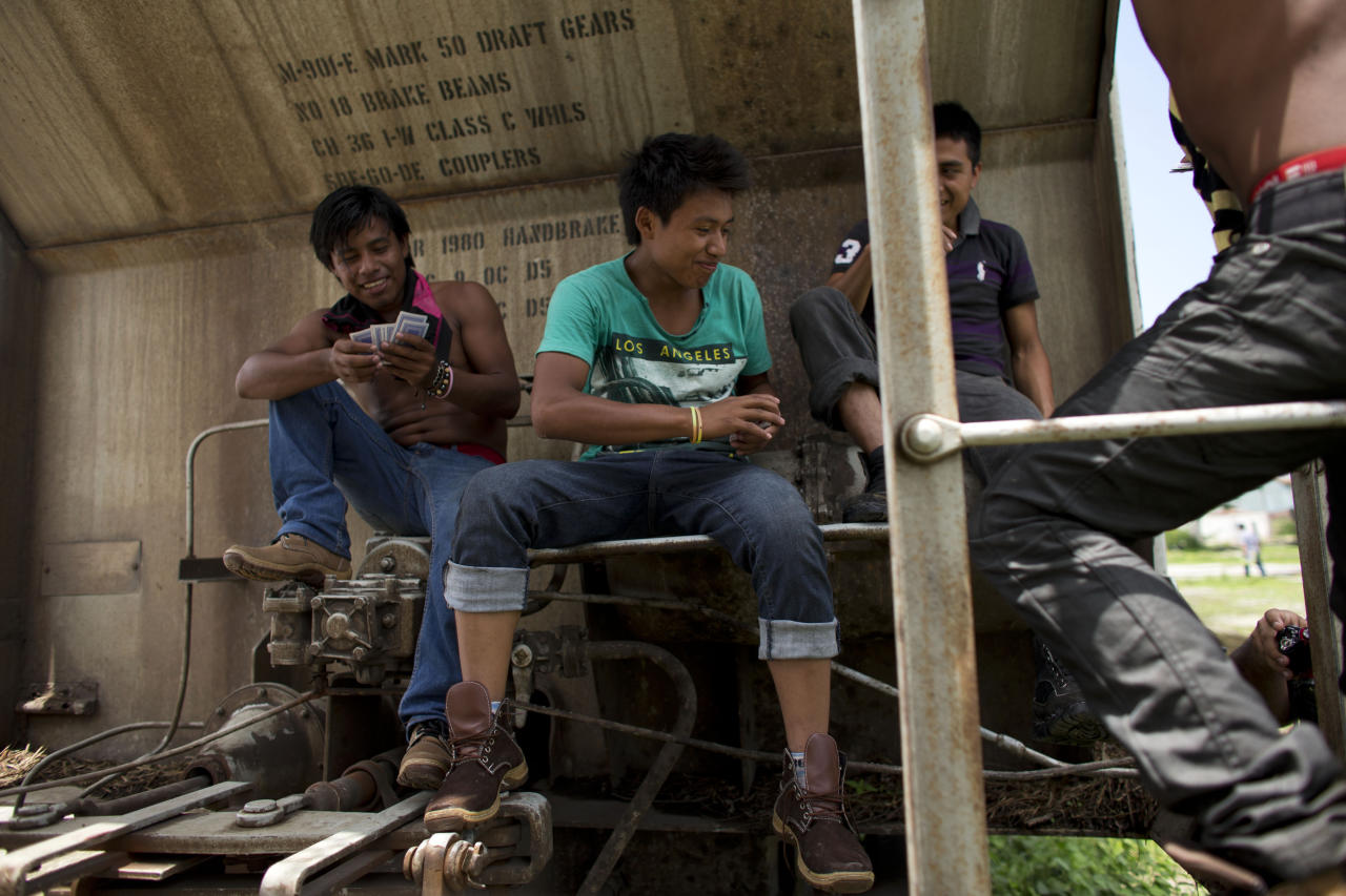 In this June 19, 2014 photo, young Central American migrants traveling together play cards on a parked boxcar as they wait for a northbound freight train at the station in Arriaga, Chiapas state, Mexico. United Nations officials are pushing for many of the Central Americans fleeing to the U.S. to be treated as refugees displaced by armed conflict, a designation meant to increase pressure on the United States to accept tens of thousands of people currently ineligible for asylum. (AP Photo/Rebecca Blackwell)