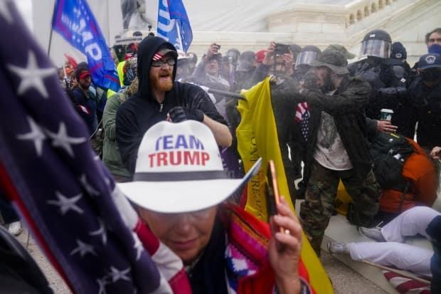 People are shown trying to break through a police barrier at the Capitol in Washington on Jan. 6. There have been about 400 arrests so far around the country in connection with the events in Washington that day.