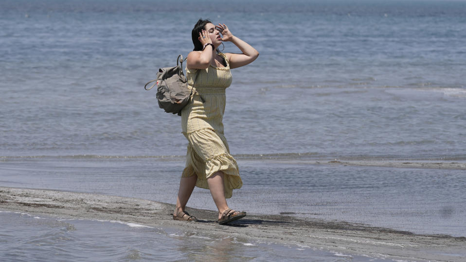 Amelia Gotbetter walks along the Great Salt Lake Tuesday, June 15, 2021, near Salt Lake City. Salt Lake City set another heat record Tuesday, June 15, 2021, and experienced its hottest day of the year as the state's record-breaking heat wave persists. Utah's capitol hit 104 degrees, breaking the previous heat record for that date of 103 degrees, according to information from the National Weather Service. On Monday, Salt Lake City hit 103 degrees to break a heat record for that date set nearly 50 years ago. (AP Photo/Rick Bowmer)