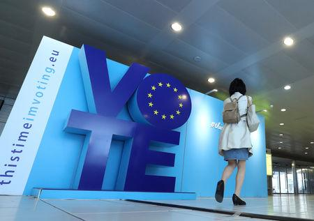 A woman walks past an advertising board for the EU elections at the Schuman railway station near the European Parliament in Brussels, Belgium, May 22, 2019. REUTERS/Yves Herman