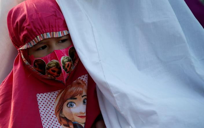 A face mask-wearing girl attends Eid al-Adha prayers on the street in Jakarta yesterday - Reuters