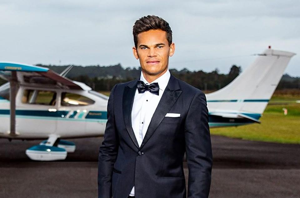 The Bachelor Australia 2021 Jimmy Nicholson wearing a tuxedo in front of a light aircraft. Photo: Channel 10.