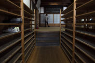 """A tourist walks past shoe racks provided for visitors at Tenryuji Temple in the Arashiyama district of Kyoto, Japan, March 18, 2020. """"Arashiyama is empty,"""" is a new catchphrase that appeared on posters in the area. """"It's time to visit Kyoto,"""" they say, because there are no long lines and waiting to do river rafting, get into popular temples or cross the bridge. (AP Photo/Jae C. Hong)"""