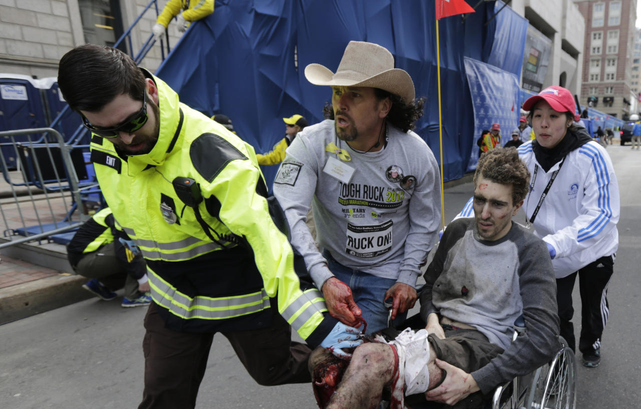 An emergency responder and volunteers, including Carlos Arredondo in the cowboy hat, push Jeff Bauman in a wheel chair after he was injured in an explosion near the finish line of the Boston Marathon Monday, April 15, 2013 in Boston. At least three people were killed, including an 8-year-old boy, and more than 170 were wounded when two bombs blew up seconds apart. (AP Photo/Charles Krupa)