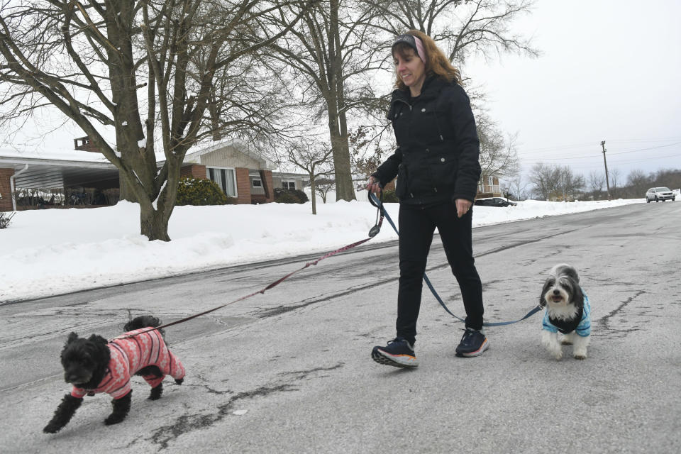 Lisa Haas, of Orwigsburg, Pa., walks her dogs Maggie, left, and Charlie, right, along Washington Street as her daughter Olivia Haas goes for a run around Stoyer's Dam in Schuylkill Haven, Pa., on Friday afternoon, Feb. 12, 2021. (Jacqueline Dormer/Republican-Herald via AP)