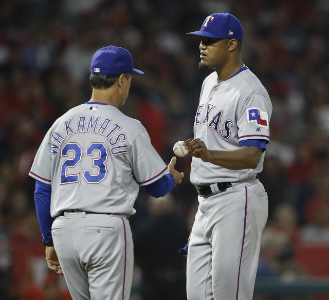 Texas Rangers starting pitcher Yohander Mendez, right, hands the ball to interim manager Don Wakamatsu during the fifth inning of the team's baseball game against the Los Angeles Angels in Anaheim, Calif., Wednesday, Sept. 26, 2018. (AP Photo/Alex Gallardo)