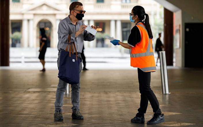 A commuter is handed a face mask by a worker in Sydney, New South Wales, Australia, 03 January 2021. Mandatory mask restrictions are in place for many venues across greater Sydney as New South Wales works to contain COVID-19 outbreaks while avoiding harsh lockdown measures. Coronavirus pandemic in New South Wales, Australia, - Shutterstock