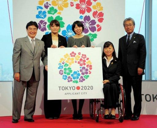 This handout picture, released from the Tokyo 2020 bid committee in 2011 shows (R-L) Japanese Olympic Committee President Tsunekazu Takeda, Paralympian swimmer Mayumi Narita, designer Ai Shimamine display the logo mark for the 2020 Olympic Games as Tokyo bids to host the 2020 Olympics