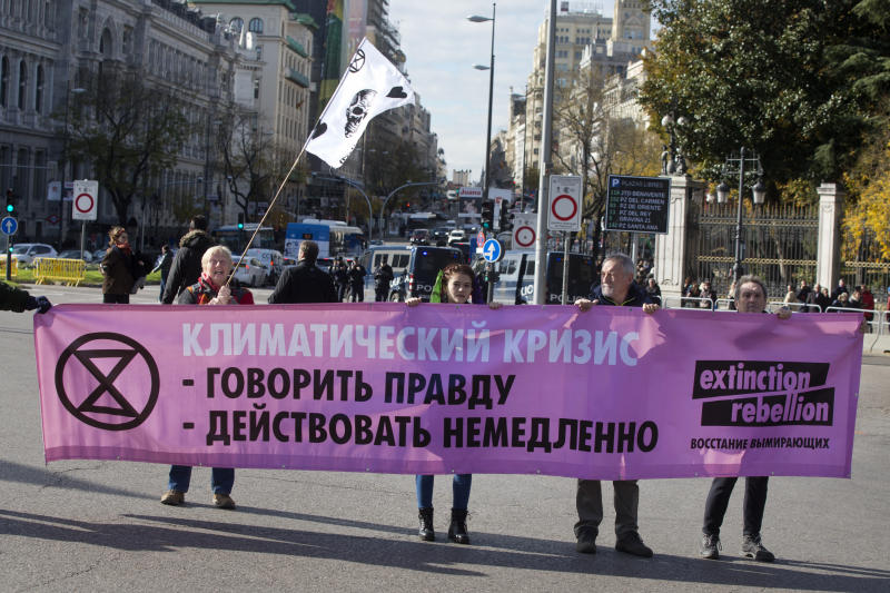 "Activists hold a banner written in the Russian language during a protest performance at the Cibeles fountain in central in Madrid, Spain, Tuesday, Dec. 3, 2019. Some 20 activists from the international group called Extinction Rebellion cut off traffic in central Madrid and staged a brief theatrical performance to protest the climate crisis. The activists held up a banner in Russian that read ""Climate Crisis. To speak the truth. To take action immediately."" (AP Photo/Paul White)"