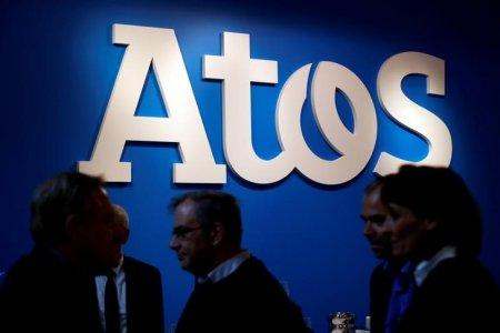 FILE PHOTO - People walk in front of Atos company's logo during a presentation of the new Bull sequana supercomputer in Paris, France, April 12, 2016. REUTERS/Philippe Wojazer/File Photo