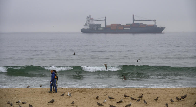 MATOSINHOS, PORTUGAL - SEPTEMBER 19: A couple walks surrounded by seagulls in Matosinhos beach while Container ship Ludwig Schulte is seen through the afternoon fog while sailing to the port of Leixoes on September 19, 2019 in Matosinhos, Portugal. The Port of Leixões is the largest port infrastructure in the Northern Region of Portugal and one of the most important in the Country. (Photo by Horacio Villalobos#Corbis/Corbis via Getty Images)
