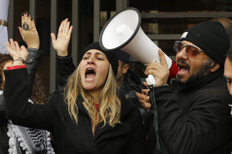 Protesters chant slogans during ongoing protests against the Lebanese political class, in front of the building of the Lebanese Association of Banks in Beirut, Lebanon, Thursday, Dec. 26, 2019. (AP Photo/Bilal Hussein)
