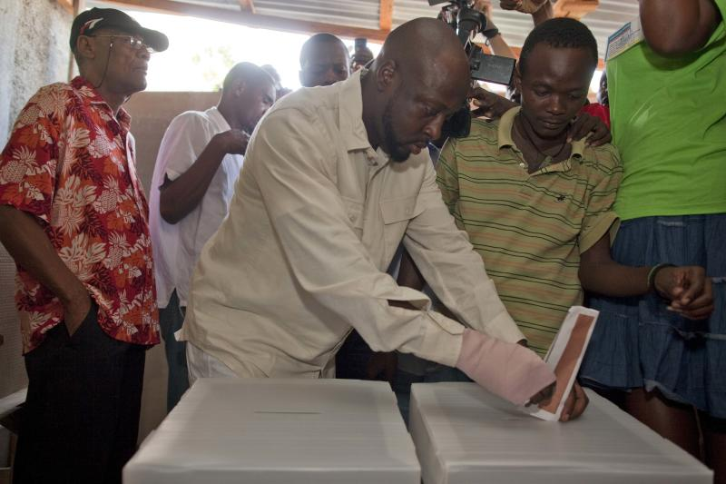 """With a bandage in his right hand, Haitian-American singer Wyclef Jean, center, casts his ballot at a polling station during a presidential runoff in Port-au-Prince, Haiti, Sunday, March 20, 2011. Jean told the AP in a telephone interview  he was grazed by a bullet in the hand when he stepped out of his car in Haiti to make a phone call. Haiti's voters will choose between candidates Mirlande Manigat, the former first lady, and Michel """"Sweet Micky"""" Martelly, a star of Haitian music to lead the country.  (AP Photo/Ramon Espinosa)"""