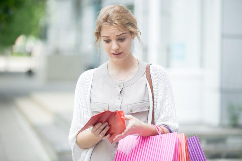 Woman Holding Shopping Bags And Looking At Wallet In Shock