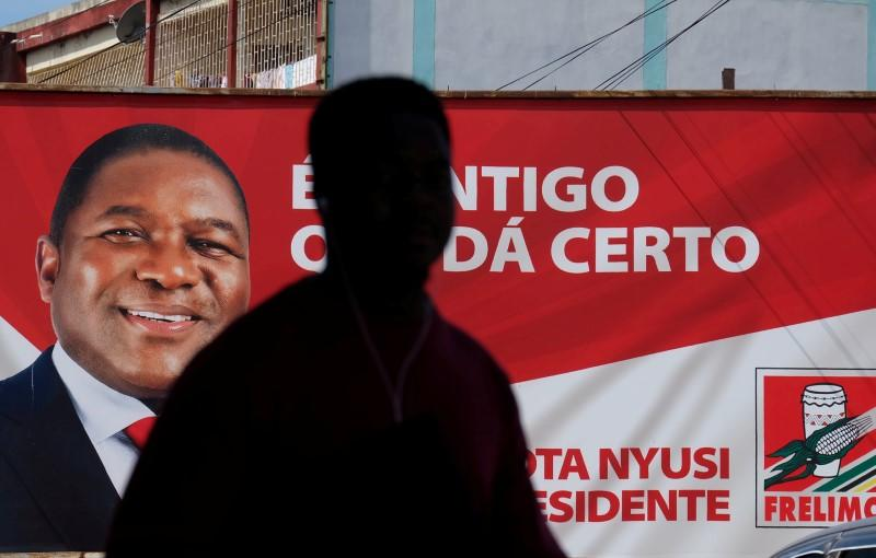 FILE PHOTO: A local walks past a billboard with a picture of Mozambique's president and leader of the Frelimo Party, Filipe Nyusi, ahead of Tuesday's provincial and legislative elections