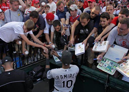 Chicago White Sox shortstop Alexei Ramirez signs autographs for the fans before a baseball game against the St. Louis Cardinals, Wednesday, June 13, 2012, in St. Louis. (AP Photo/Tom Gannam)