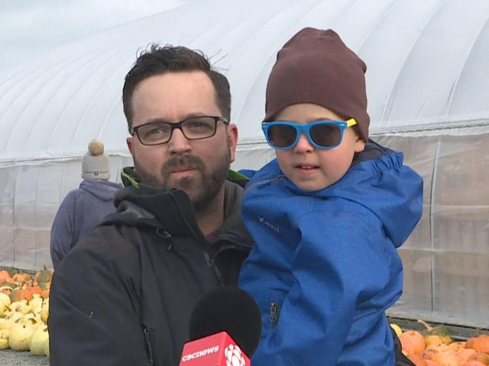 Stephen Penney and his son, Issac, spent part of Sunday in search of the perfect pumpkins for Halloween. (Emma Grunwald/CBC - image credit)