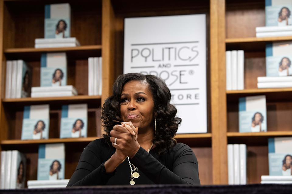TOPSHOT - Former US first lady Michelle Obama meets with fans during a book signing on the first anniversary of the launch of her memoir