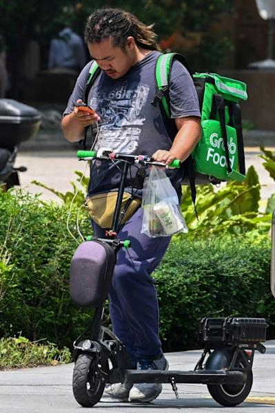 Singapore's transport ministry says the government and companies are offering grants for e-scooter delivery riders to switch to other devices including regular and power-assisted bicycles