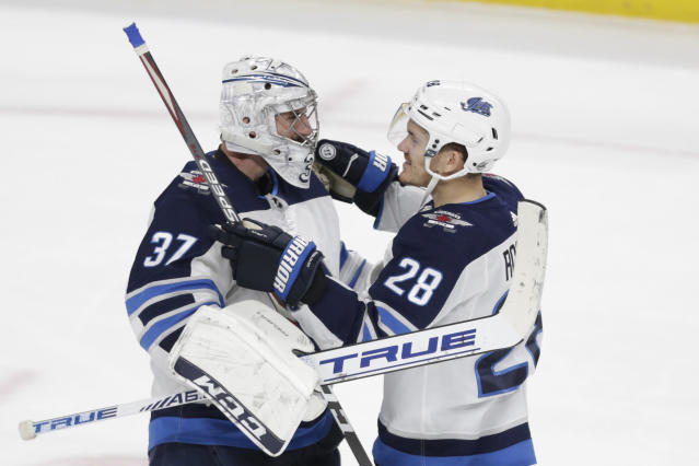 Winnipeg Jets goalie Connor Hellebuyck (37) is congratulated by teammate Jack Roslovic (28) after defeating the Minnesota Wild in an NHL hockey game Saturday, Dec. 21, 2019, in St. Paul, Minn. The Jets defeated the Wild 6-0. (AP Photo/Andy Clayton-King)