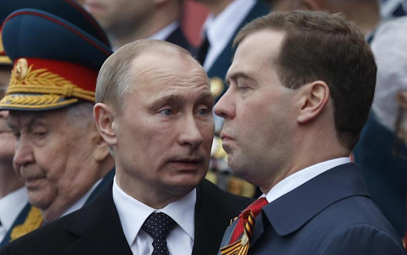 Russian President Vladimir Putin, left, speaks to Prime Minister Dmitry Medvedev on the Red Square, during the Victory Day Parade, which commemorates the 1945 defeat of Nazi Germany in Moscow, Russia, Wednesday, May 9, 2012. Putin told the annual massive military parade in Red Square that the country will stand up for its positions.(AP Photo/Alexander Zemlianichenko)