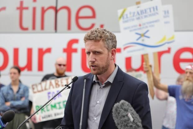 Liberal Leader Iain Rankin speaks in Amherst, N.S., on Tuesday, July 20, 2021, with protesters standing behind him. (Rob Short/CBC - image credit)