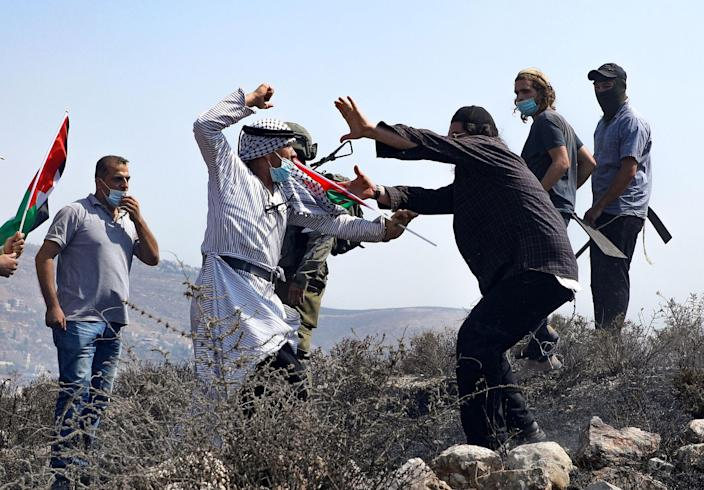 Image: Palestinians protesting against Jewish settlements and the normalisation of ties with two Arab states, scuffle with Israeli settlers in Asira al-Qibliya in the Israeli-occupied West Bank, (Jaafar Ashityeh / AFP - Getty Images)
