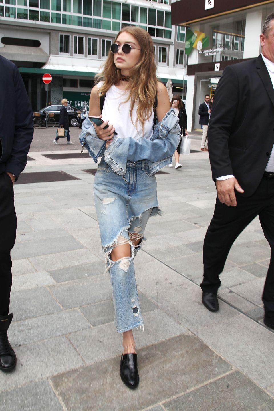 <p>In a RE/DONE | Hanes muscle tee, denim jacket, destroyed high-waisted jeans with layered fabric accents, black Freda Salvador mules, rounded sunglasses, a printed Frasier Sterling choker and a backpack.</p>