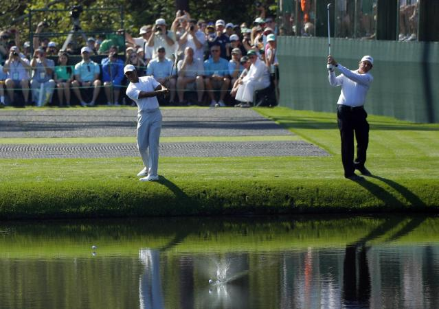 U.S. golfers Tiger Woods (L) and Phil Mickelson skip balls off the water towards the 16th green during the second day of practice for the 2018 Masters golf tournament at Augusta National Golf Club in Augusta, Georgia, U.S. April 3, 2018. REUTERS/Brian Snyder