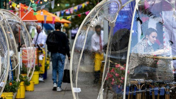 FILE PHOTO: A woman sits outside Cafe Du Soleil under bubble tents used during the novel coronavirus pandemic in Manhattan, New York City, on Sept. 23, 2020. (Jeenah Moon/Reuters)