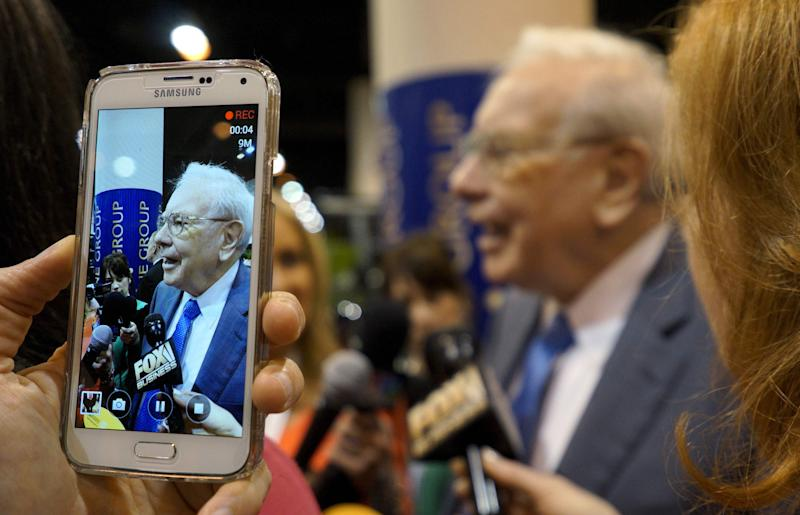 Berkshire Hathaway CEO Warren Buffett is seen on a cellphone camera as he talks to reporters prior to the Berkshire annual meeting in Omaha, Nebraska May 2, 2015. REUTERS/Rick Wilking