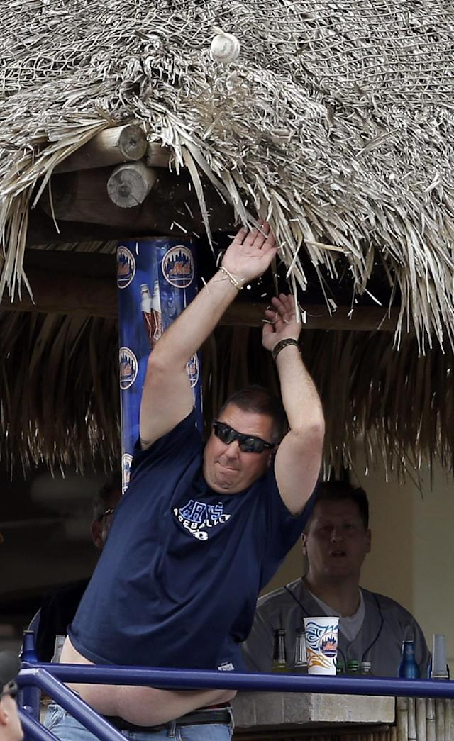 A man tries to catch a line drive foul ball as it bounces off the roof of a stadium bar during an exhibition spring training baseball game between the St. Louis Cardinals and the New York Mets Friday, March 7, 2014, in Port St. Lucie, Fla. (AP Photo/Jeff Roberson)