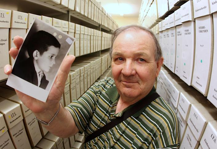 George Jaunzemis, 69, who was separated from his mother in the final days of World War II, displays a photograph that shows him as a child at the International Tracing Service in Bad Arolsen, germany, on Thursday, May 19, 2011 after discovering his true identity. (Michael Probst)
