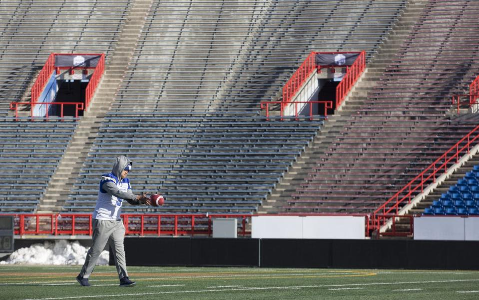 Football player stands in empty stadium
